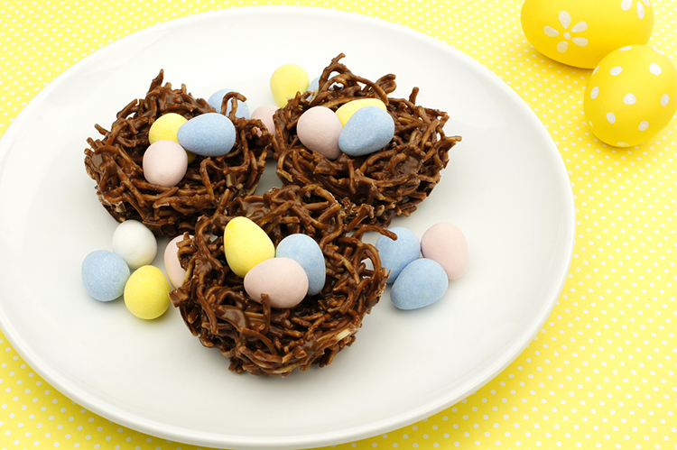 Plate of springtime chocolate nests filled with Easter eggs on a yellow background