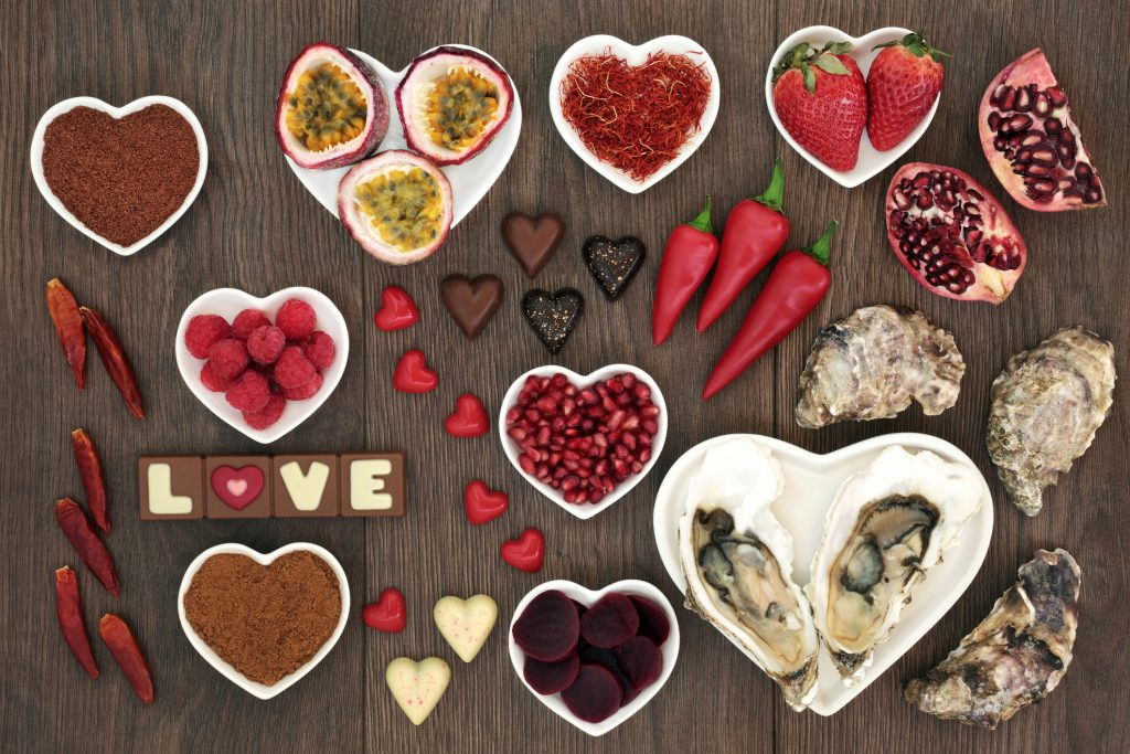 Aphrodisiac food for sexual health with foods in heart shaped bowls and loose on oak wood background.